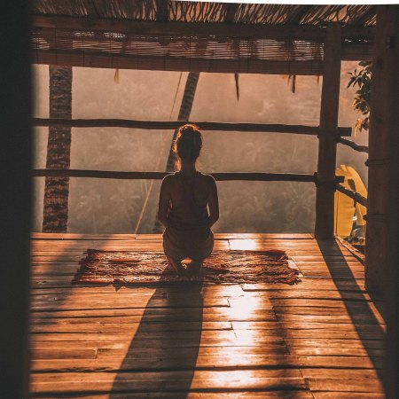 Meditation at sunset in a rainforest hut